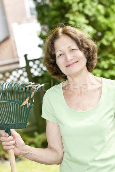 Kıdemli kadın tırmık gülümseyen bahçıvanlık Stok fotoğraf © elenaphoto