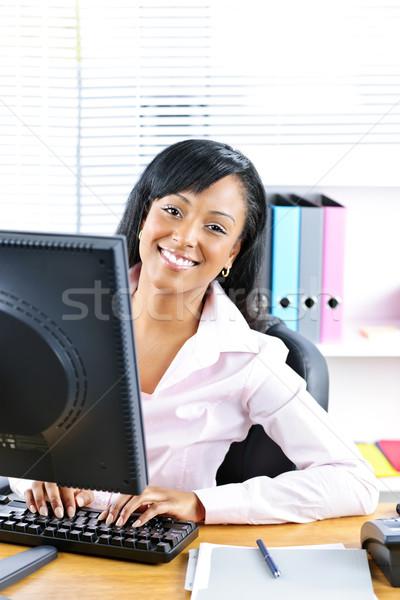 Happy black businesswoman at desk Stock photo © elenaphoto