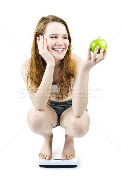 Young smiling girl on bathroom scale holding apple Stock photo © elenaphoto