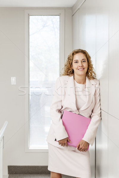 Businesswoman standing in office hallway Stock photo © elenaphoto