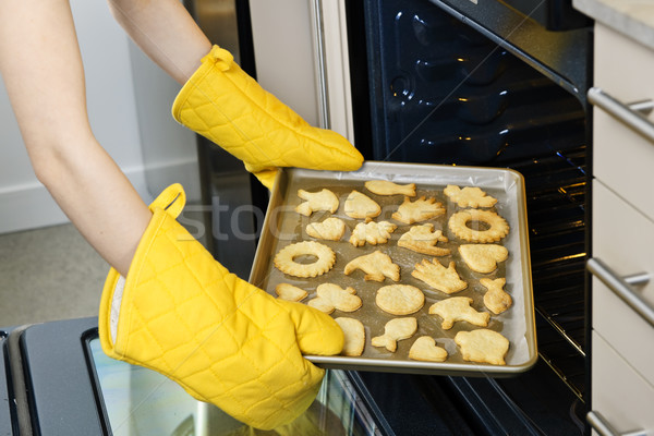 Taking cookies from oven Stock photo © elenaphoto
