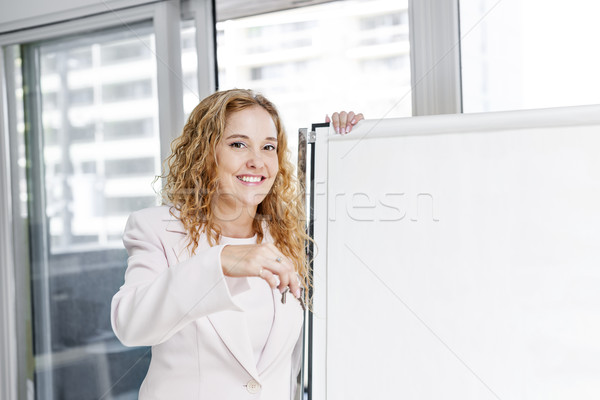 Real estate agent with keys and flip chart Stock photo © elenaphoto