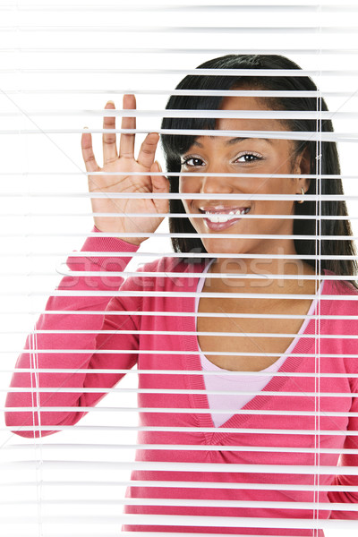 Stock photo: Smiling woman looking through blinds