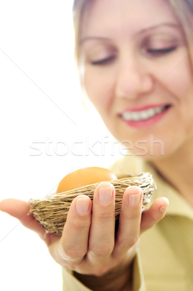 Mature woman holding a nest with an egg Stock photo © elenaphoto