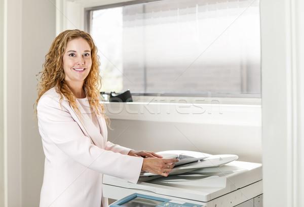 üzletasszony fénymásoló iroda mosolyog üzletasszony gép Stock fotó © elenaphoto
