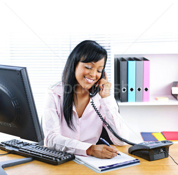 Smiling black businesswoman on phone at desk Stock photo © elenaphoto
