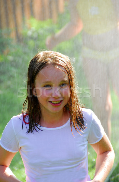 Girl and sprinkler Stock photo © elenaphoto