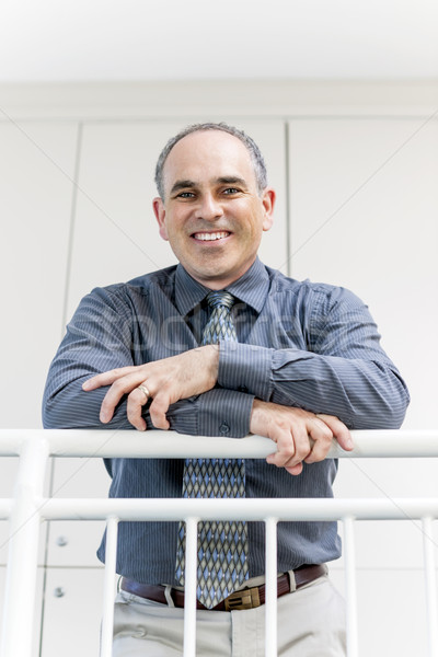 Businessman standing in office hallway smiling Stock photo © elenaphoto