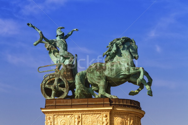Statue representing War, a man holding a snake on a chariot, on a colonnade in Heroes Square or Hoso Stock photo © Elenarts