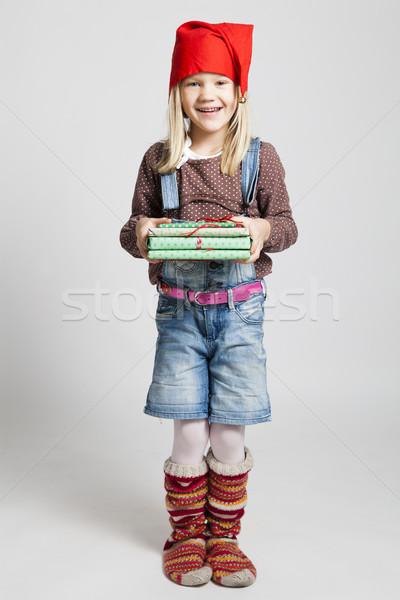 Smiling girl holding Christmas presents Stock photo © ElinaManninen