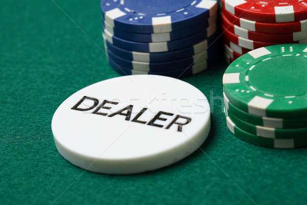 Dealer button and poker chips on a green surface. Stock photo © ElinaManninen