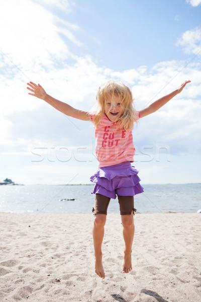 Fiatal lány ugrik tengerpart aranyos boldog homok Stock fotó © ElinaManninen