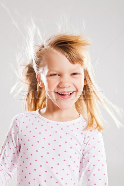 Szczęśliwy uśmiechnięty młoda dziewczyna studio portret wiatr Zdjęcia stock © ElinaManninen