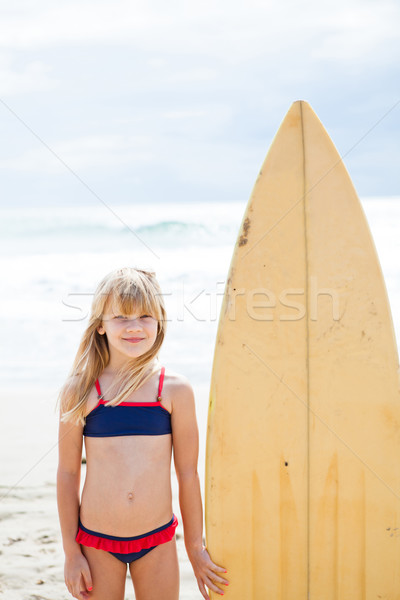Smiling young girl standing next to surfboard Stock photo © ElinaManninen