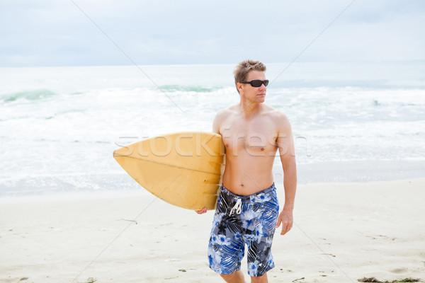 серьезный глядя человека ходьбе доска для серфинга пляж Сток-фото © ElinaManninen
