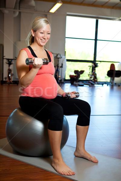 Kobieta w ciąży wagi mięśni hantle Zdjęcia stock © ElinaManninen