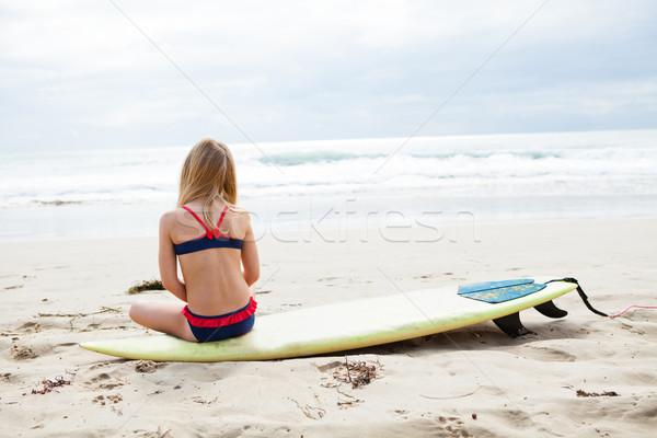 Fiatal lány ül szörfdeszka tengerpart fiatal szőke Stock fotó © ElinaManninen