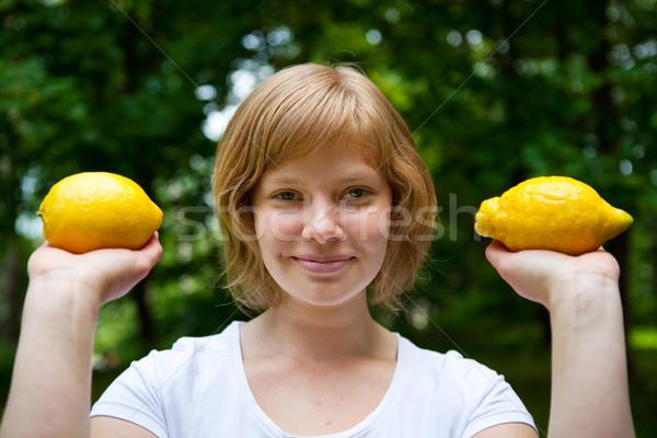 Lány tart citromok mosolyog kettő kint Stock fotó © ElinaManninen