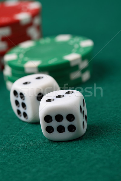 Pair of gambling die and poker chips on a green surface. Stock photo © ElinaManninen
