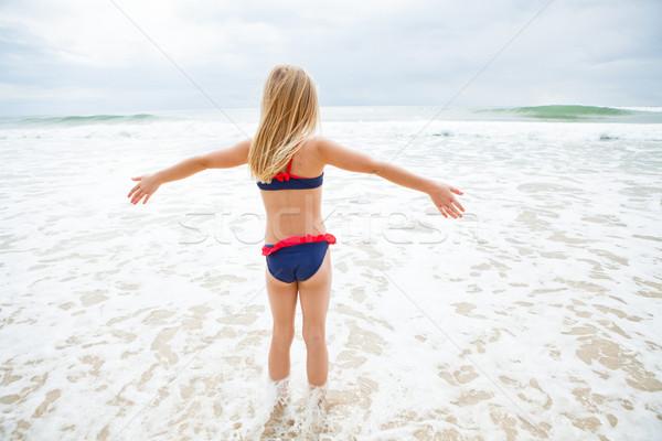 Fiatal lány áll víz tengerpart aranyos szemben Stock fotó © ElinaManninen