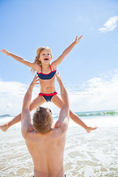 Father throwing young daughter in air at beach Stock photo © ElinaManninen