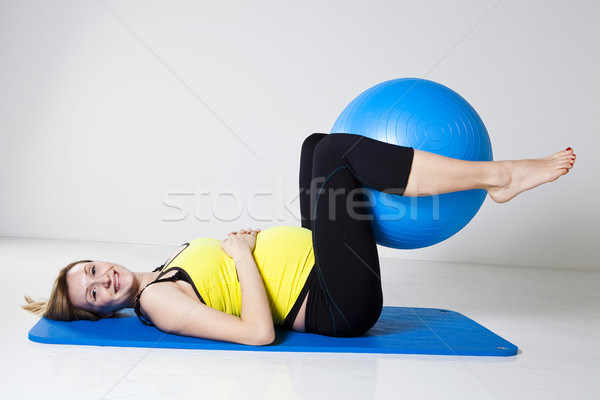 Stock photo: Pregnant woman exercising with fitness ball