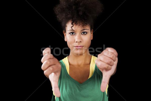 Nő hüvelykujjak lefelé gyönyörű sportos stúdiófelvétel Stock fotó © ElinaManninen