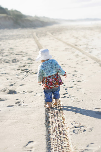 Stock photo: Little girl walking along a tire track on a beach.