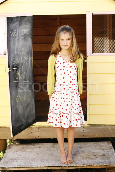 Portrait of a pretty young girl standing outside her playhouse. Stock photo © ElinaManninen
