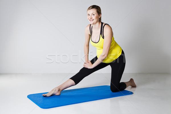 Pregnant woman performing leg stretch Stock photo © ElinaManninen