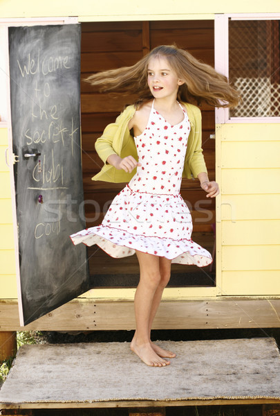 Stock photo: Pretty young girl spinning around outside her playhouse.