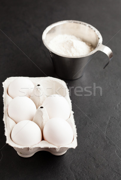 Eggs and cup of flour Stock photo © ElinaManninen