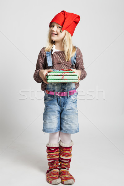 Smiling girl holding Christmas gifts Stock photo © ElinaManninen