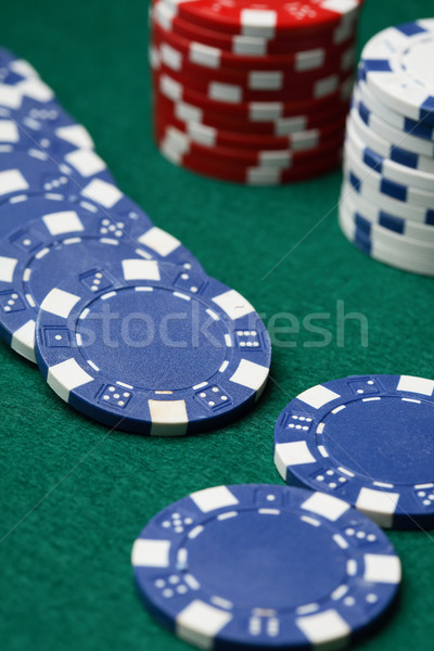 Poker chips spread out over a green surface. Stock photo © ElinaManninen