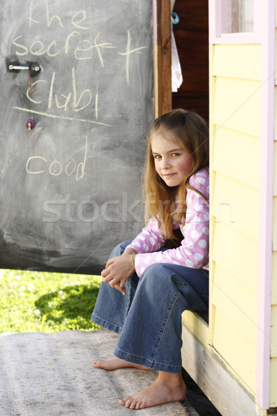 Pretty young girl sitting at her playhouse. Stock photo © ElinaManninen
