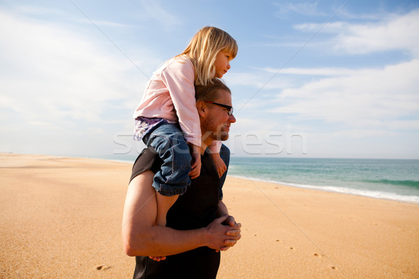 Father carrying daughter on shoulders at the beach Stock photo © ElinaManninen