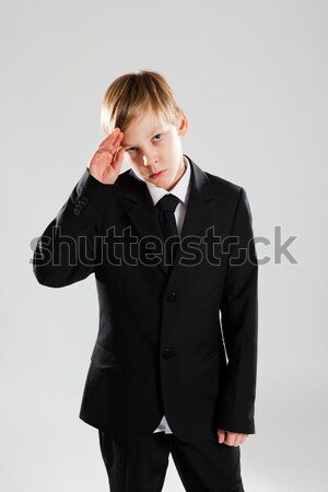 Serious young boy in black suit saluting Stock photo © ElinaManninen