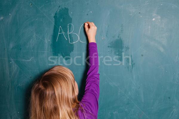 Młoda dziewczyna piśmie litery Tablica alfabet kredy Zdjęcia stock © ElinaManninen