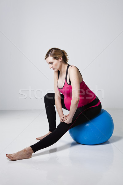 Pregnant woman stretching with fitness ball Stock photo © ElinaManninen