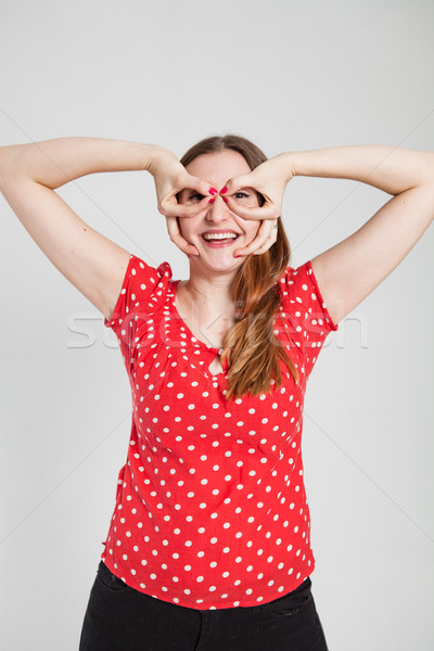 Smiling attractive woman through finger goggles Stock photo © ElinaManninen