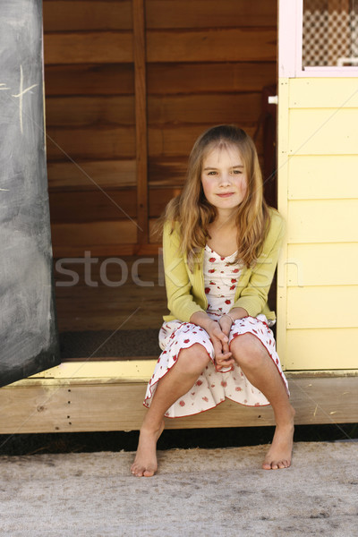 Portrait of a pretty young girl sitting outside her playhouse. Stock photo © ElinaManninen
