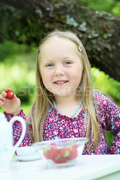 Smiling little girl a tea party. Stock photo © ElinaManninen