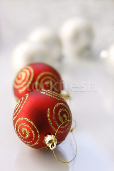 Red and silver colored Christmas baubles on a glass table. Stock photo © ElinaManninen