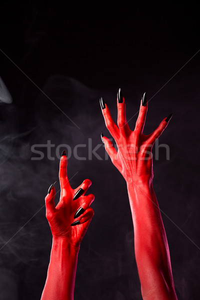Spooky red devil hands with black nails   Stock photo © Elisanth