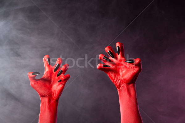 Spooky red devil hands with black glossy nails   Stock photo © Elisanth