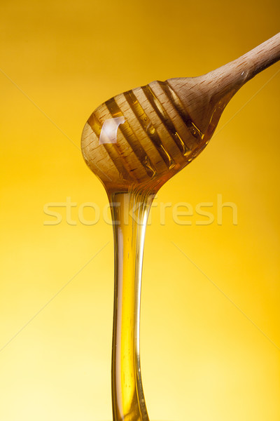 Close-up shot of wooden drizzler and flowing honey  Stock photo © Elisanth