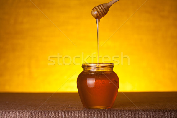 Stock photo: Honey jar with dipper and flowing honey