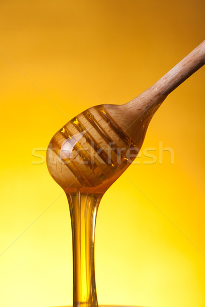 Close-up shot of wooden drizzler with flowing honey  Stock photo © Elisanth