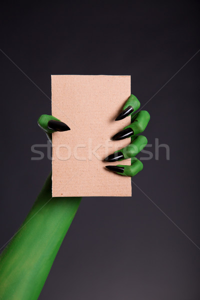 Green monster hand with black nails holding blank piece of cardb Stock photo © Elisanth