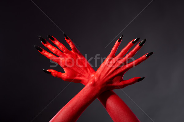 Crossed red devil hands with black nails   Stock photo © Elisanth